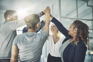 Shot of a diverse group of coworkers high fiving together in an office